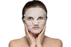 Beautiful young woman is applying a cosmetic mask on a face on a white background stock images