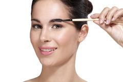 Beautiful young woman applying eyebrow brush Royalty Free Stock Photos