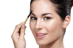 Beautiful young woman applying eyebrow brush Stock Photos