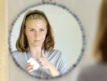 Beautiful young woman applying face cream Stock Photography