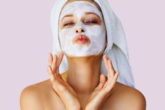 Beautiful young woman applying facial mask on her face. Skin care and treatment, spa, natural beauty and cosmetology concept stock photo