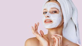 Beautiful young woman applying facial mask on her face. Skin care and treatment, spa, natural beauty and cosmetology concept. Over pastel lavender background stock photo
