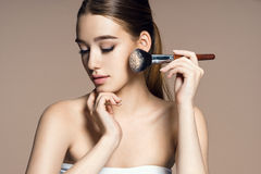 Beautiful young woman applying foundation on her face with tassel. Royalty Free Stock Photography