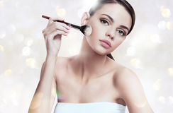 Beautiful young woman applying foundation on her face with tassel, skin care concept Stock Photo