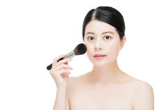 Beautiful young woman applying foundation powder blush with make Royalty Free Stock Photography