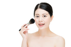 Beautiful young woman applying foundation powder blush with make Royalty Free Stock Photo