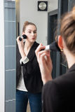 Beautiful young woman applying her blush or face powder before mirror. Beautiful young woman with a business jacket standing in front of a chic mirror applying Royalty Free Stock Photo
