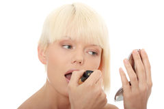 A beautiful young woman applying her make-up Royalty Free Stock Photos