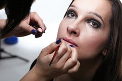 Beautiful young woman applying lips make-up zone Stock Photos