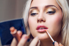 Beautiful young woman applying lips makeup with cosmetic brush Royalty Free Stock Photography