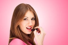 Beautiful young woman applying lipstick Royalty Free Stock Image