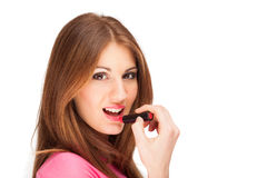 Beautiful young woman applying lipstick Royalty Free Stock Images