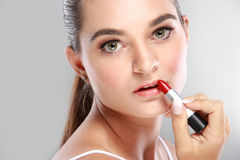 Beautiful young woman applying lipstick Royalty Free Stock Photos