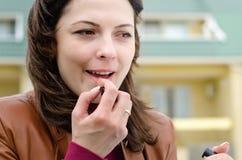 Beautiful young woman applying lipstick Stock Image