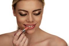 Beautiful young woman applying lipstick Royalty Free Stock Image