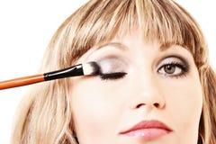 Beautiful young woman applying makeup Royalty Free Stock Photos