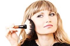 Beautiful young woman applying makeup Stock Photography