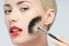 Beautiful Young Woman Applying Makeup with Brush Royalty Free Stock Photography