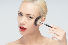 Beautiful Young Woman Applying Makeup with Brush Royalty Free Stock Images