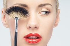 Beautiful Young Woman Applying Makeup with Brush Royalty Free Stock Photo