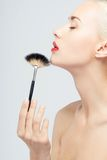 Beautiful Young Woman Applying Makeup with Brush Stock Images