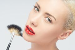 Beautiful Young Woman Applying Makeup with Brush Royalty Free Stock Image