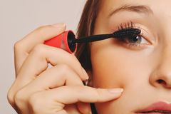 Beautiful young woman applying mascara. Royalty Free Stock Photography