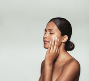 Beautiful young woman applying moisturizer to her face Stock Images