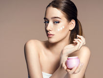 Beautiful young woman applying moisturizing creme Stock Photography