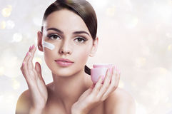 Beautiful young woman applying moisturizing creme, skin care concept Royalty Free Stock Photos