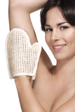Beautiful young woman applying scrub glove on her perfect skin Royalty Free Stock Photo