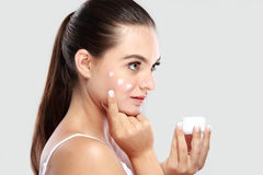 Beautiful young woman applying some facial cream on her cheek Royalty Free Stock Images
