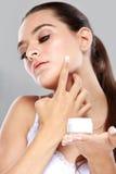 Beautiful young woman applying some facial cream Stock Photo