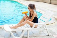 Beautiful young woman applying sun block cream on leg. Girl in b. Lack bikini sitting on sun bed in the pool blackground Royalty Free Stock Photo
