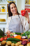 Beautiful young woman in apron holding a paprika and smiling whi Stock Image
