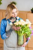 Beautiful young woman in apron holding vase with tulips in flower. Shop royalty free stock photos