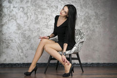 Beautiful young woman in a armchair. Black dress, shoes and stockings Stock Image