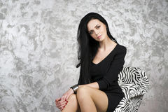 Beautiful young woman in a armchair Stock Photos