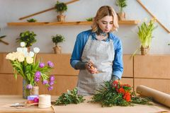 Beautiful young woman arranging flowers in flower. Shop royalty free stock image