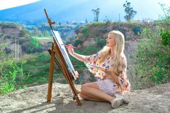 Beautiful young woman artist paints a landscape in nature. Drawing on the easel with colorful paints in the open air. Painting in nature, plein air royalty free stock photos