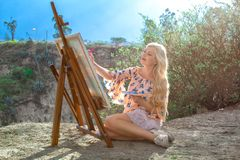 Beautiful young woman artist paints a landscape in nature. Drawing on the easel with colorful paints in the open air. Painting in nature, plein air royalty free stock image