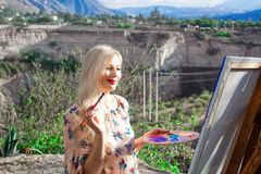 Beautiful young woman artist paints a landscape in nature. Drawing on the easel with colorful paints in the open air. Painting in nature, plein air stock images