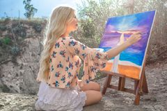 Beautiful young woman artist paints a landscape in nature. Drawing on the easel with colorful paints in the open air. Painting in nature, plein air stock photos