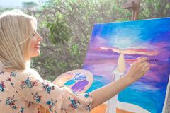 Beautiful young woman artist paints a landscape in nature. Drawing on the easel with colorful paints in the open air. Painting in nature, plein air stock image