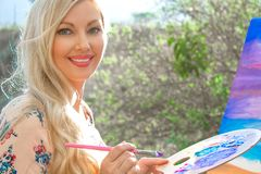 Beautiful young woman artist paints a landscape in nature. Drawing on the easel with colorful paints in the open air. Painting in nature, plein air royalty free stock photo