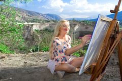 Beautiful young woman artist paints a landscape in nature. Drawing on the easel with colorful paints in the open air. Painting in nature, plein air royalty free stock photography