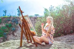 Beautiful young woman artist paints a landscape in nature. Drawing on the easel with colorful paints in the open air. Painting in nature, plein air stock photography