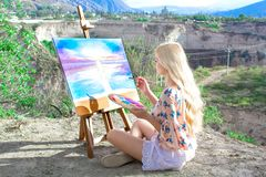 Beautiful young woman artist paints a landscape in nature. Drawing on the easel with colorful paints in the open air. Painting in nature, plein air stock photo