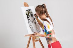 Woman painter soiled in colorful paint draws on canvas. Royalty Free Stock Image