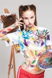 Woman painter soiled in colorful paint draws on canvas. Royalty Free Stock Photos